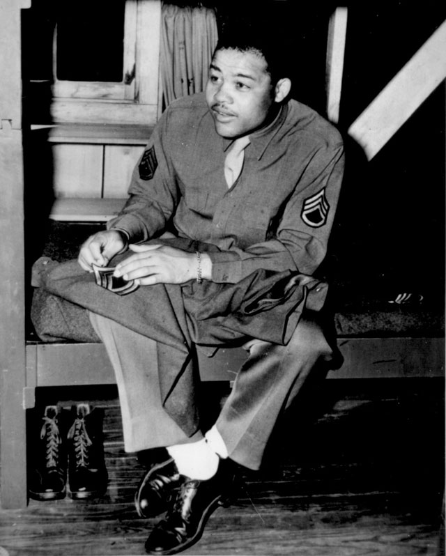 World Heavyweight champ Joe Louis (Barrow) sews on the stripes of a technical sergeant--to which he has  been promoted. April 10, 1945. 208-PU-120V-12.