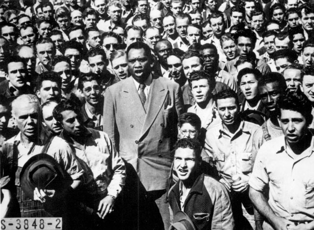 Paul Robeson, world famous Negro baritone, leading Moore Shipyard [Oakland, CA] workers in singing the  Star Spangled Banner, here at their lunch hour recently, after he told them: 'This is a serious job--winning this war against fascists. We have to be together.'  Robeson himself was a shipyard worker in World War I. September 1942.  Wide World Photos. 208-NS-3848-2.