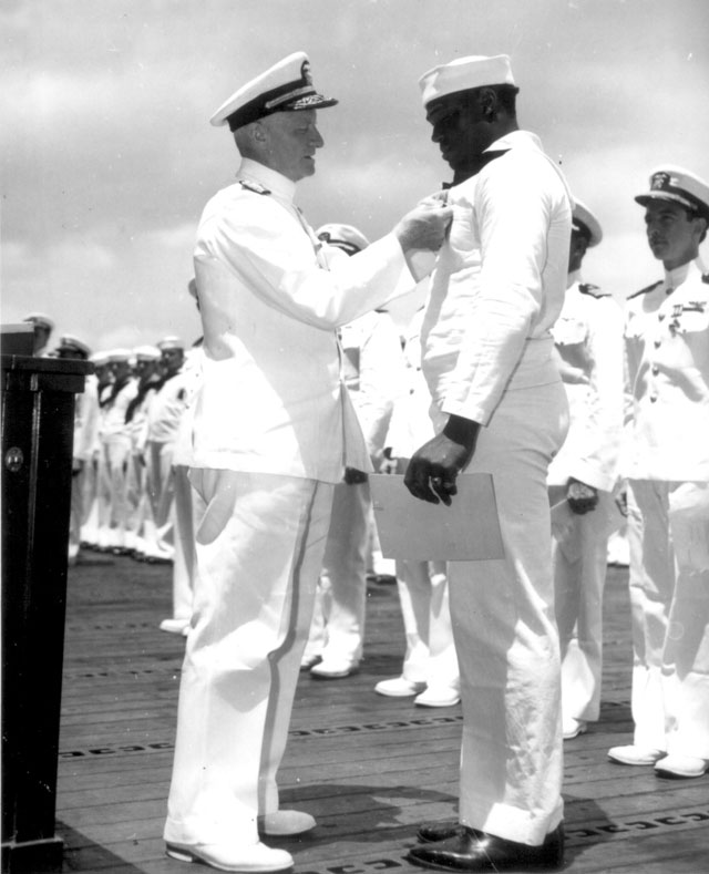 Admiral C. W. Nimitz, CinCPac, pins Navy Cross on Doris Miller, at ceremony on board warship in Pearl Harbor,  T. H. May 27, 1942. 208-NP-8PP-2