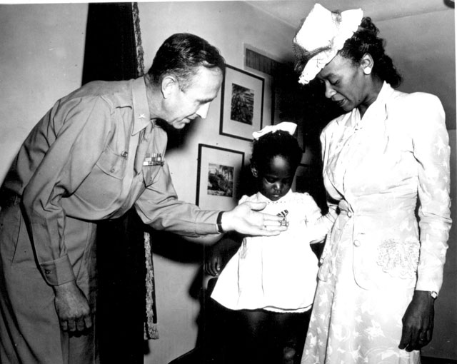 Brig. Gen. Robert N. Young, Commanding General of the Military District of Washington, assists Melba Rose,  aged 2, daughter of Mrs. Rosie L. Madison, in viewing the Silver Star posthumously awarded her father  1st Lt. John W. Madison, of the 92nd Infantry Division, who was killed in action in Italy   N.d. 208-AA-139B-1.