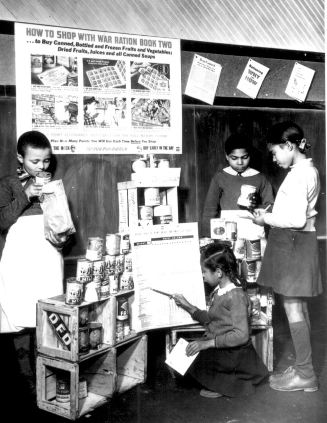 To learn how to shop with point stamps, these youngsters in a Fairfax County, Virginia, grade school have set  up a play store, complete with point value table and informational material  on point rationing. N.d. Roger Smith.  208-NP-4FFF-1