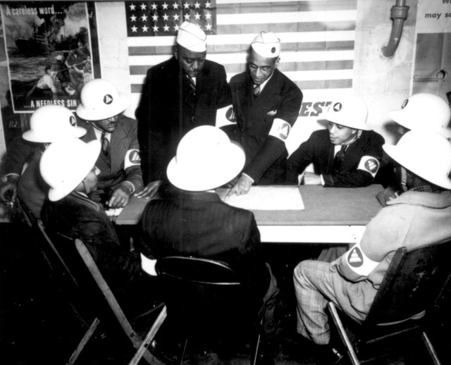 Air raid wardens at a sector meeting in Washington, DC, discuss the zones they control during a practice air raid.  N.d. Roger Smith. 208-NP-4W-3.