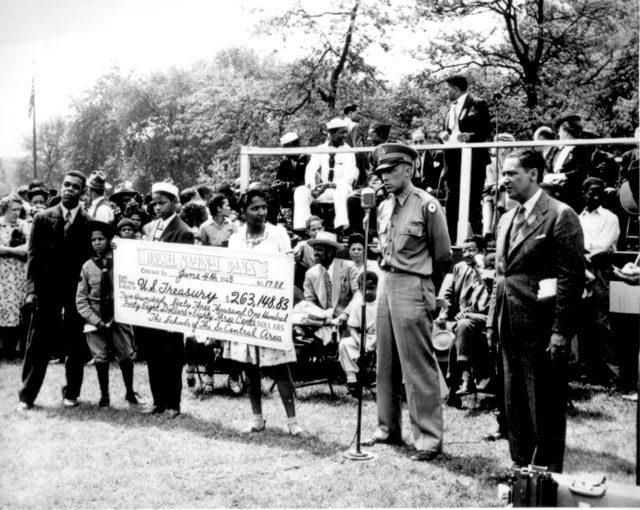The public school children of the South-Central District of Chicago purchased $263,148. 83 in war bonds  and stamps a huge check representing enough money for 125 jeeps, two pursuit  planes and motorcycle was presented to Maj. C. Udell Turpin of the Illinois War Bond Sales staff.  N.d. 208-NP-3MM-1.