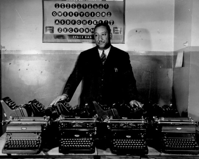 Cortez W. Peters, World's Champion Portable Typist, is shown with ten late model standard-size typewriters  which he turned over to the Government to aid the drive for 600,000 machines for the Army and Navy. November 1942.  Danor. 208-NP-1V-1.