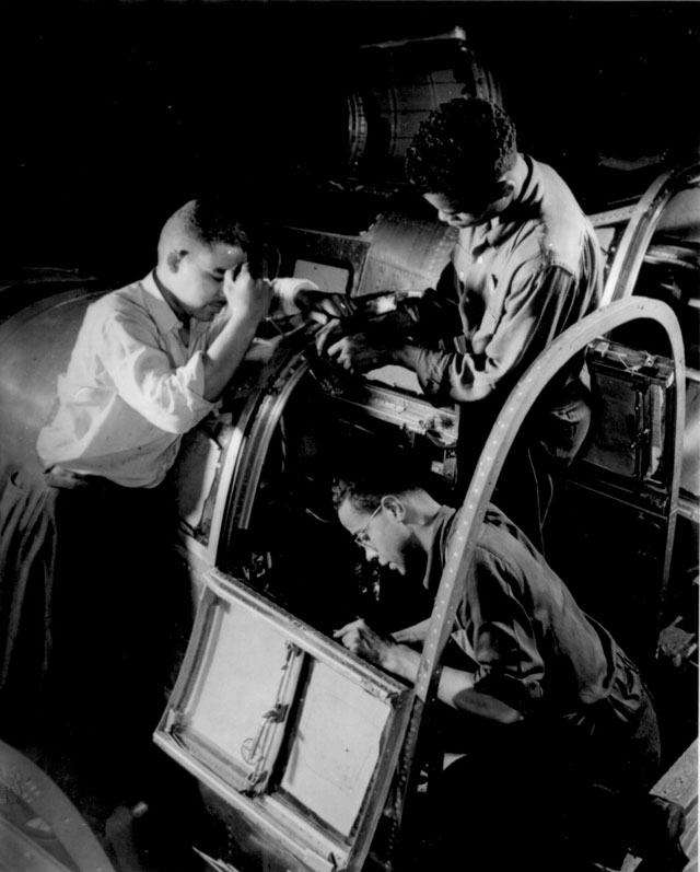 Final assembly of the pilot's compartment is being made by these Negro workers in a large eastern aircraft factory.  These youths went directly from a war training course to their jobs in this plant. May 1942.  Howard Liberman 208-NP-2VV-2.