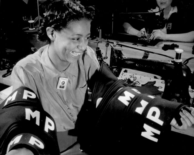 Insignia for military police are being turned out in an eastern quartermaster corps depot where this young worker  has obtained war production employment. May 1942. Howard Liberman. 208-NP-2HHH-1.