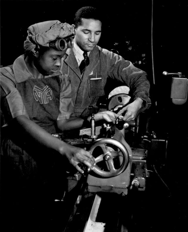 Under the direction of Cecil M. Coles, NYA foreman, Miss Juanita E. Gray learns to operate a lathe machine at  the Washington, DC, NYA War Production and Training Center.  This former domestic worker is one of hundreds of Negro women trained at this center.  N.d. Roger Smith. 208-NP-2QQQQ-1.