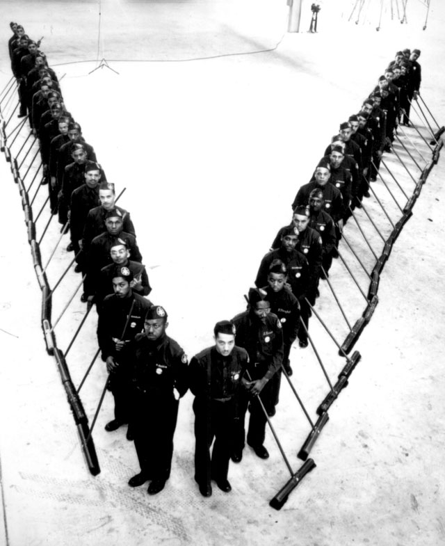 The Negro janitors of the plant maintenance department in North America's Kansas City factory in V-formation  as they start out on their daily tasks. February 4, 1942. Carl Conley. 208-NP-1KK-1.
