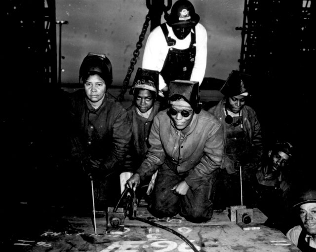 Welders Alivia Scott, Hattie Carpenter, and Flossie Burtos await an opportunity to weld their first piece of steel  on the ship [SS George Washington Carver]. Kaiser Shipyards, Richmond, CA. Ca. 1943.  E.F. Joseph. 208-NP-1HHH-5.