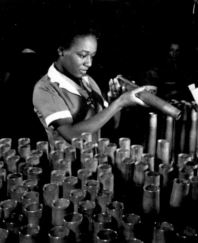 Bertha Stallworth, age 21, shown inspecting end of 40mm artillery cartridge case at Frankford Arsenal.  N.d. 208-NP-1WW-1.